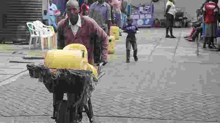 Samson Muli, 42, pai de dois filhos, trabalha como carregador de água há 18 anos em Nairóbi - Simon Maina/AFP Photo   - Simon Maina/AFP Photo