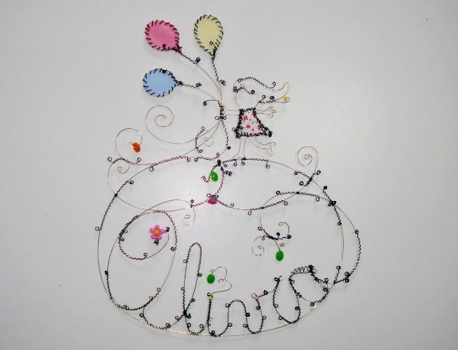 Enfeite aramado de menina com balões, da Feito Laço e Abraço (www.elo7.com.br/feitolacoeabraco). A peça mede 23 cm por 39 cm. R$ 270. Preço pesquisado em agosto de 2015 e sujeito a alterações
