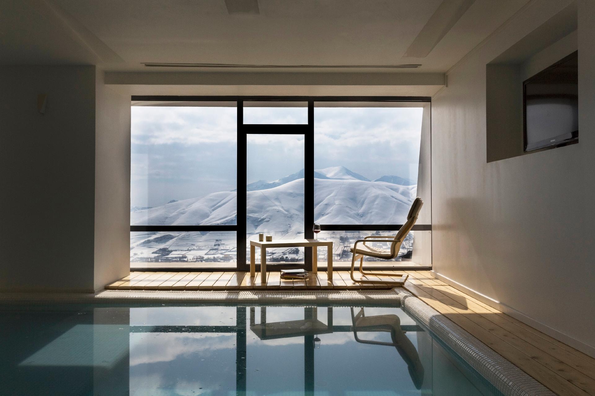 No pavimento mais baixo, onde está a área de lazer com piscina, também há uma grande esquadria que valoriza a vista para as montanhas. Aqui, o piso de madeira também é empregado e dá aconchego à casa Mosha, projetada pelo escritório iraniano New Wave Architecture