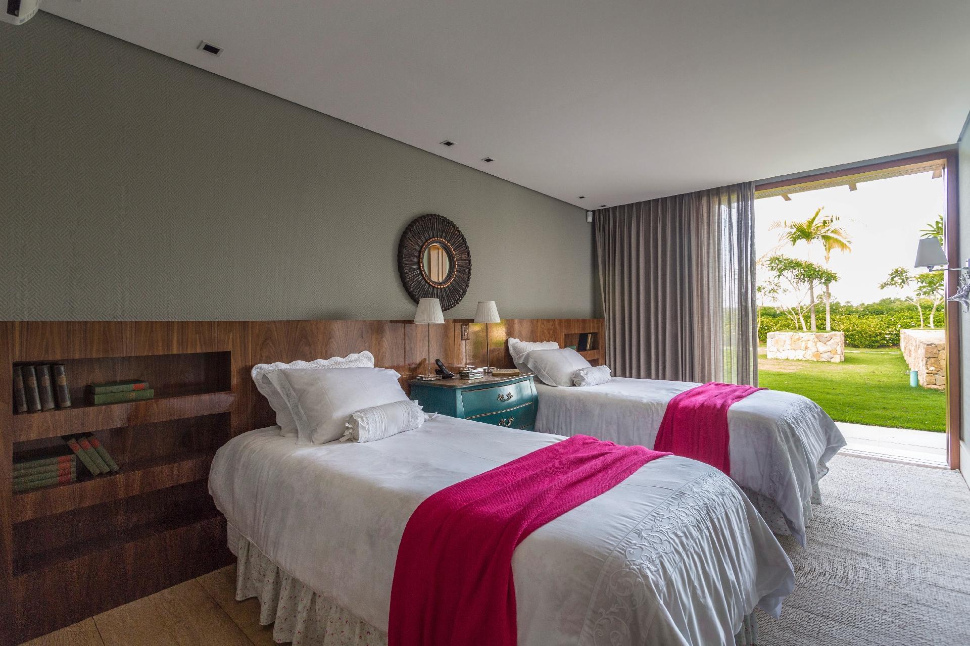 Em uma das suítes da casa de campo no interior de SP, a cabeceira em madeira (nogueira), com acabamento brilhante, recebeu nichos para acomodar os livros. O dormitório com cortinas de linho está conectado ao jardim da residência decorada pelo arquiteto Maurício Karam