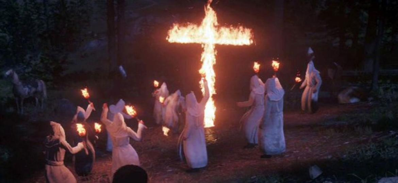 "Grupo racista Ku Klux Klan em ""Red Dead Redemption 2"" - Reprodução/Game Revolution"