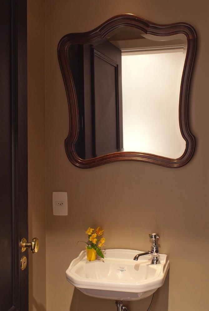 No lavabo social do Apartamento Higienópolis, o clima também é retrô, com espelho de loja de antiguidades do Bixiga, em São Paulo. A iluminação é baixa e as louças sanitárias são da linha Oxford, da Deca - de estilo mais clássico. Projeto de reforma pela D2N Arquitetura e Interiores