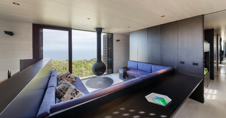 Pisos, forros e paredes internas da cabana Moonlight, na Austrália, são revestidas com um tipo de eucalipto australiano clareado. Na sala de estar, o recorte do piso na base da lareira suspensa foi feito com ardósia polida e o sofá foi contornado pela marcenaria em laminado melamínico preto. O projeto de arquitetura e interiores é do escritório Jackson Clements Burrows
