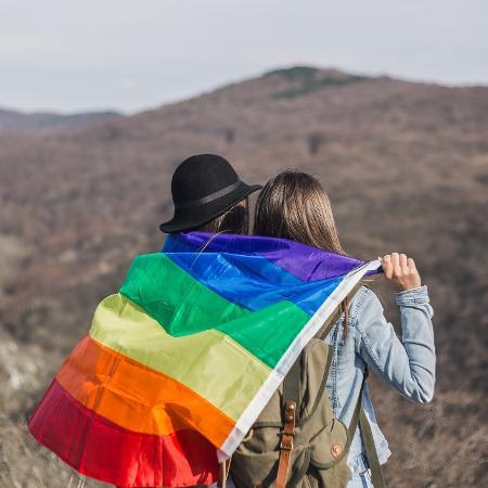 Casal de lésbicas viajando com a bandeira gay - Getty Images