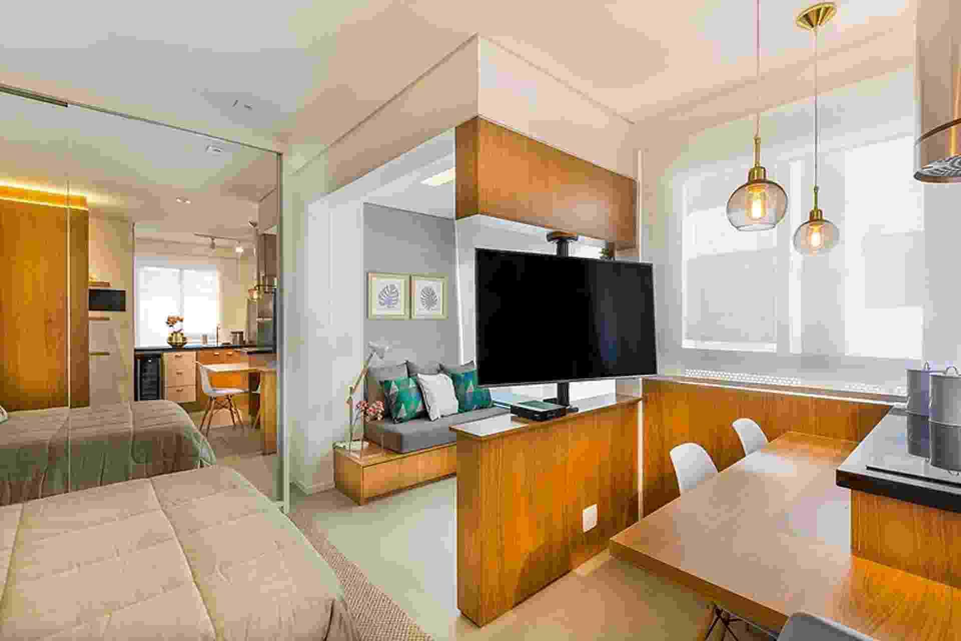 Sem paredes para dividir os 32 m², Fernanda Sebrian e Gabriella Amadei, da AS Design Arquitetura, precisaram resolver onde apoiariam a TV. A solução foi uma coluna feita de marcenaria que apoia o aparelho e permite que ele gire em 360º. Dessa forma, sala, quarto e até cozinha são contemplados - Samuel Alexandre/ Divulgação
