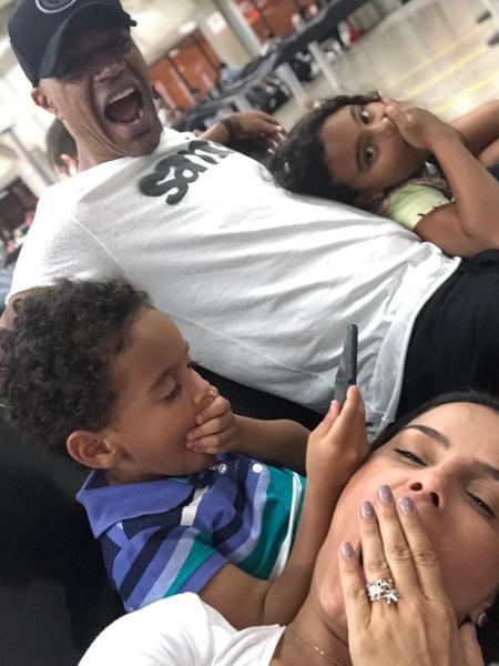 Denílson e Luciele Di Camargo esperam no aeroporto ao lado dos filhos - Reprodução/Instagram
