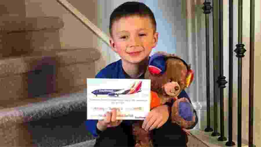 Grayson com seu novo ursinho de pelúcia dado pela Southwest Airlines - Reprodução