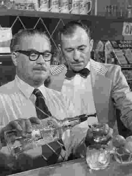 Bartender mostra ao colega como preparar gim tônica, em foto de 1958 - Denver Post via Getty Images