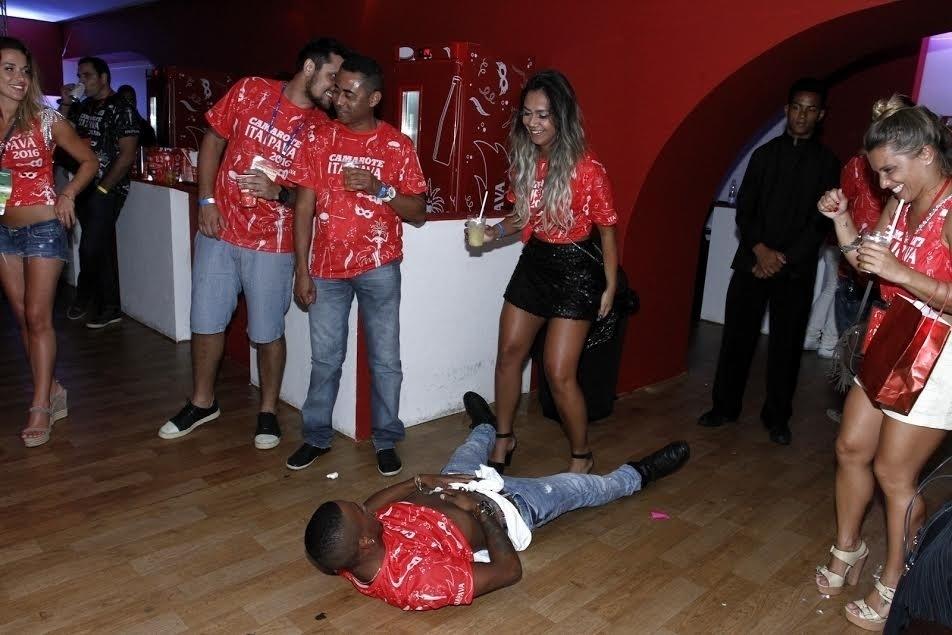 9.fev.2016 - Deitado no chão do camarote, Nego do Borel levanta a camisa e olha para morena