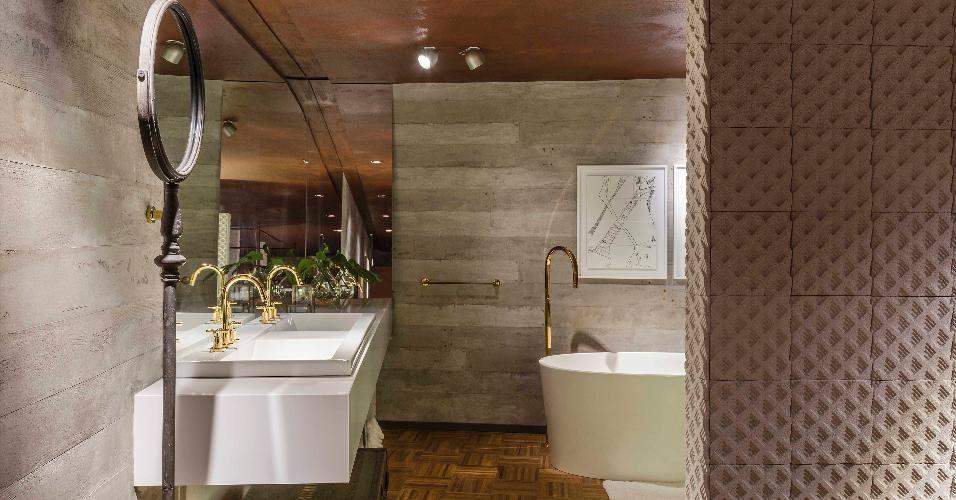 Casa Cor Brasília 2016 - No banheiro da Morada Sáinz, de Eduardo Sáinz e Lilian Glayna Sáinz, o metal é usado de maneiras diversas e proporciona diferentes efeitos. Em primeiro plano, o espelho redondo é sustentado pelo pedestal metálico opaco e cinzento, que remete à decoração industrial e retrô.  Ao fundo, os metais sanitários e o toalheiro têm acabamento dourado e acrescentam um toque luxuoso