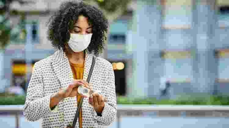 máscara, álcool em gel, cuidados, covid, pandemia, mulher de máscara usando alcool em gel - Getty Images - Getty Images