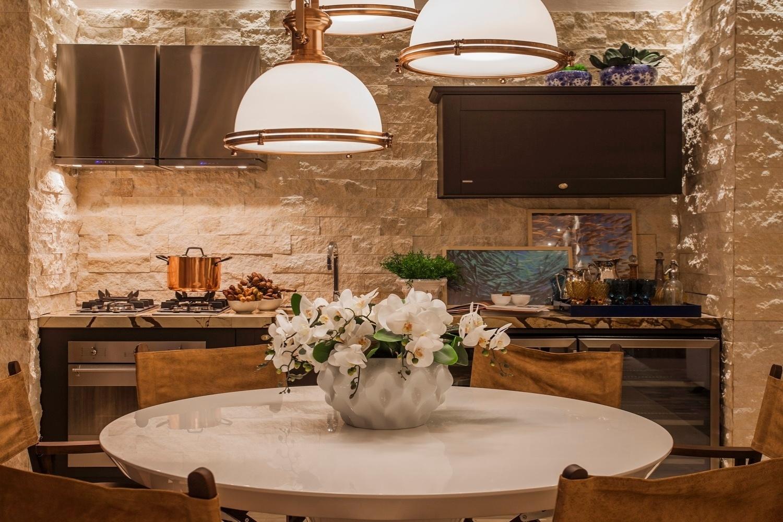 Integrada à cozinha, a sala de jantar da Casa de Praia tem mesa laqueada e cadeiras estruturadas em madeira com encostos de couro. Sobre o conjunto, a luminária com três cúpulas tem detalhes dourados | O projeto assinado pela arquiteta Vanessa Martins está exposto na Casa Cor Pará (www.casacor.com.br) até 29 de novembro de 2015
