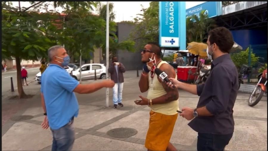 Diante de um hospital municipal, funcionário da Prefeitura (à esq.) atrapalha entrevista de um paciente a um repórter da Globo - Reprodução