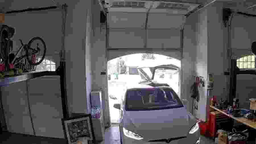 Mulher dobra porta de Tesla Model X entrando em casa - Reprodução