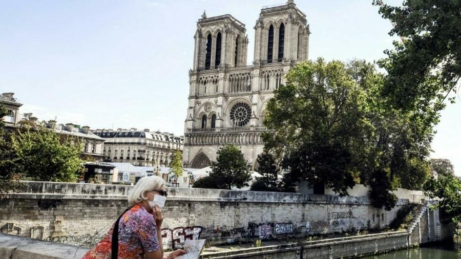 Turista na ponte Cardeal Lustiger, em frente à catedral de Notre-Dame, em Paris - AFP
