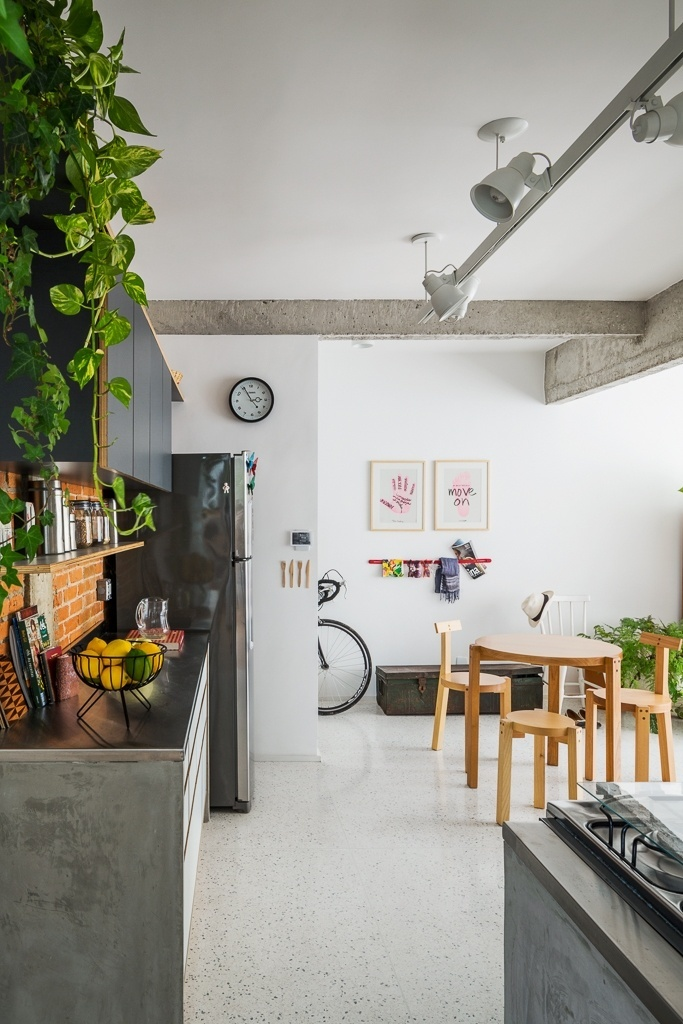 A cozinha planejada, com acabamento laminado e bancada inox, foi distribuída de modo a deixar livre a área para a sala de jantar e para a circulação. Compactas, a mesa e as cadeiras Girafa, da Marcenaria Baraúna, resolvem o espaço de refeição em estilo contemporâneo. Ao fundo, um baú antigo e a cadeira em estilo