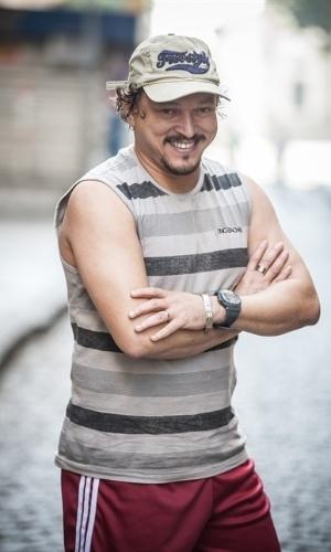 """Oziel (Fabio Lago) - Nascido e criado na Macaca, Oziel começou a trabalhar cedo como taxista e há alguns anos vem ganhando bastante dinheiro com """"transporte executivo"""" com seu próprio carro, um reluzente sedã. Há 18 anos casado com Indira (Cris Vianna) e pai de quatro filhos"""