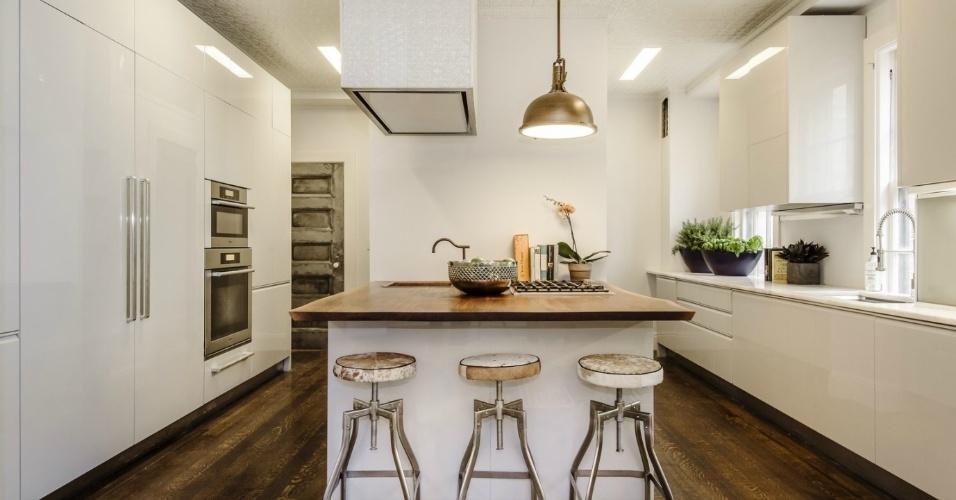 No primeiro pavimento da cobertura de Uma Thurman, à venda por R$ 22 milhões, está localizada a cozinha. O ambiente tem uma ilha de cocção central, móveis totalmente brancos, eletrodomésticos embutidos e detalhes com inspiração industrial. Ao fundo (à esq.), uma porta cinza dá acesso à biblioteca da atriz de