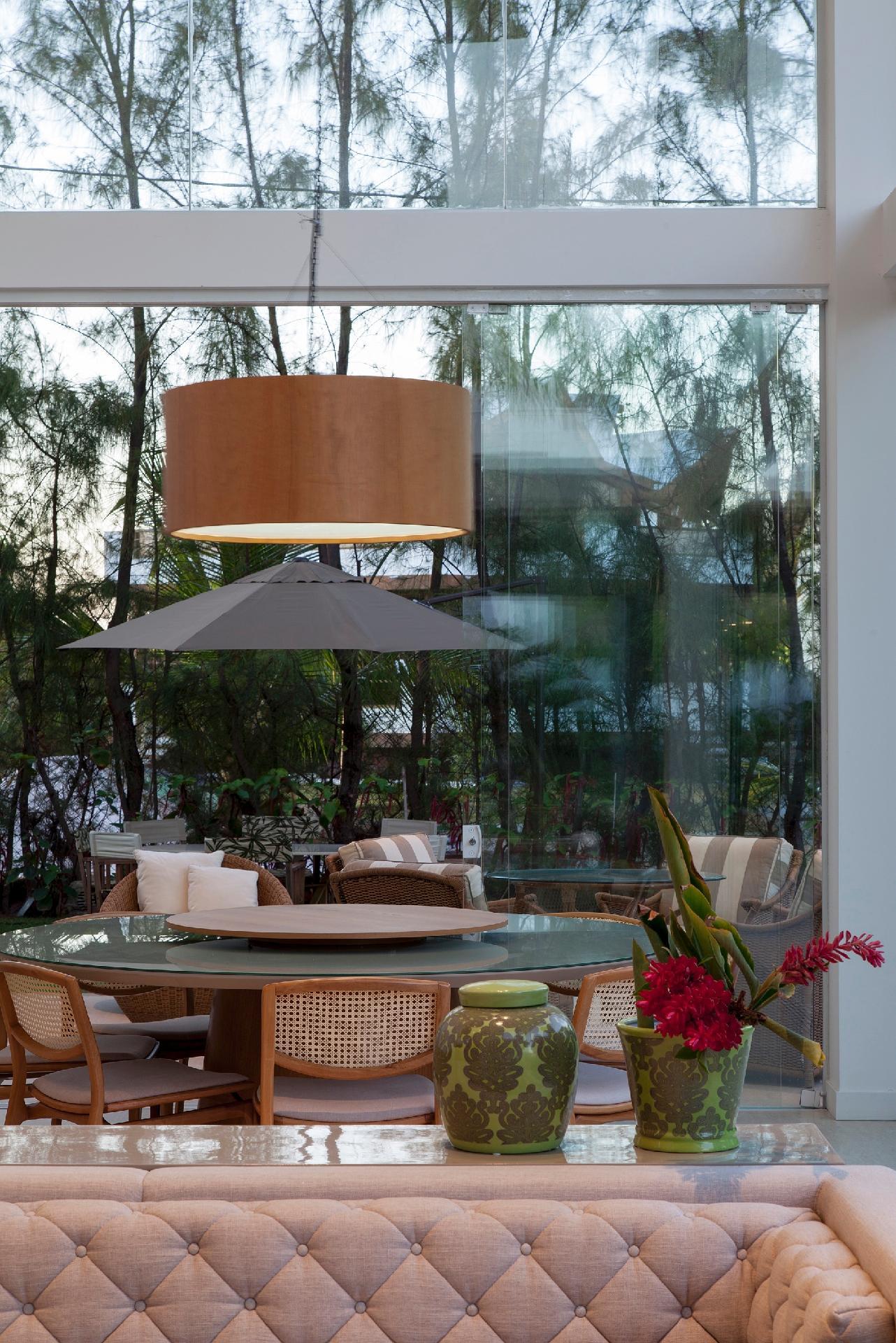 Conectada com a área externa da casa de praia, a sala de jantar é equipada com uma mesa redonda e cadeiras Alexia (Home Design Casual), com encosto de palhinha e design de Tadeu Paisan. O arquiteto Sidney Quintela assina o projeto de arquitetura e interiores desta casa em Camaçari (BA)