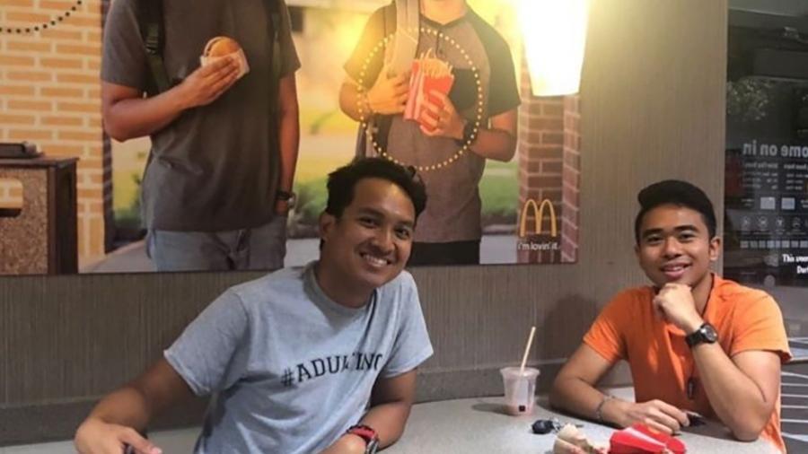 """Jevh e Christian ao lado do pôster que produziram e penduraram no McDonald""""s - Reprodução/@Jevholution"""