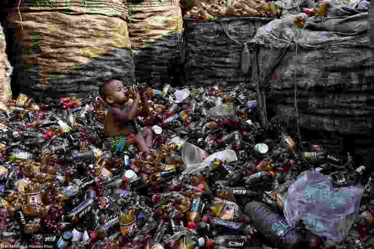 """""""Uma criança bebe de uma garrafa."""" - MD MAHABUB HOSSAIN KHAN - MD MAHABUB HOSSAIN KHAN"""