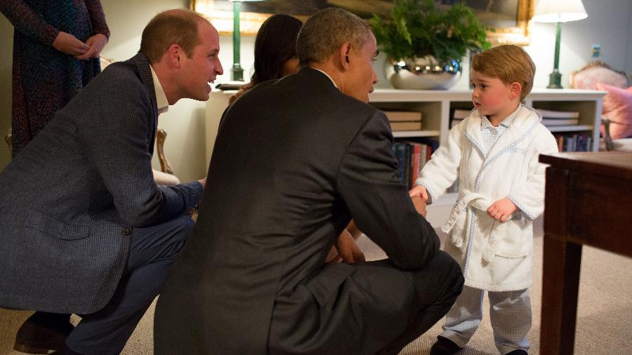 O príncipe William e o casal Obama agacham-se para falar como o príncipe George, em foto de abril deste ano - Pete Souza/AFP/Reprodução