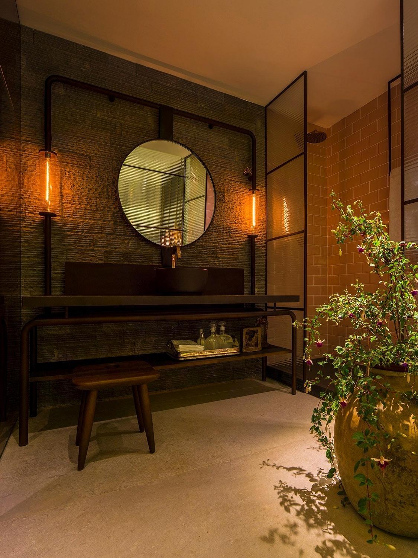 Casa Cor MG 2016 - Uma bancada com toques industriais é o xodó do banheiro da Suite da Estilista, projetada por Maurício Bonfim. As lâmpadas laterais, que remetem tanto às antigas incandescentes de filamento como aos lampiões, podem não ser a iluminação ideal para um banheiro, mas oferecem um toque decorativo charmoso para lavabos 'na vida real'