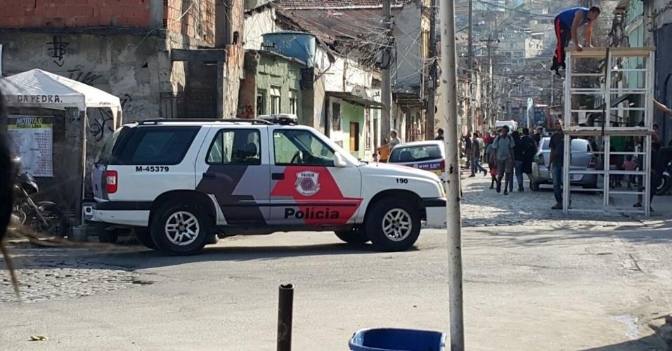 Um carro de polícia é parado em frente à cracolândia em cena que Larissa será presa e levada para uma clínica de reabilitação