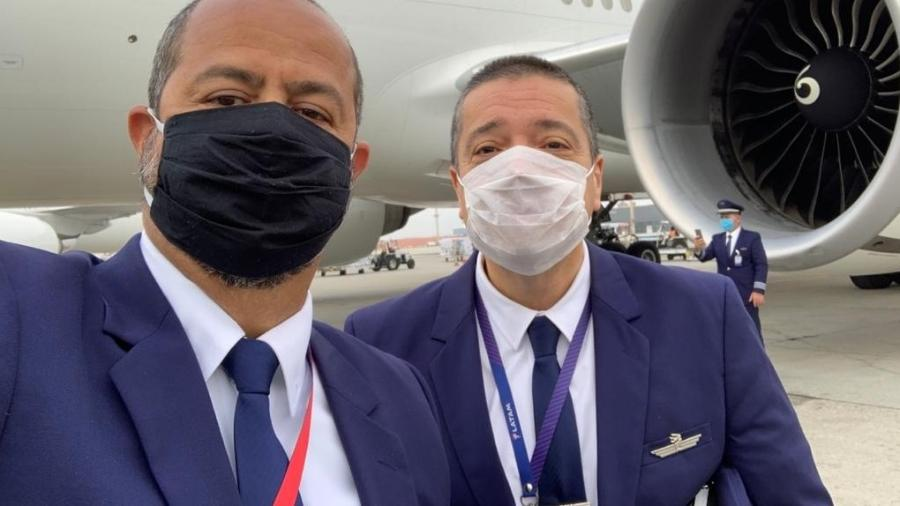 Comandante Carlos Ribeiro (à esq.) e colega se preparam para o voo que iria até a China recolher máscaras  - Arquivo pessoal