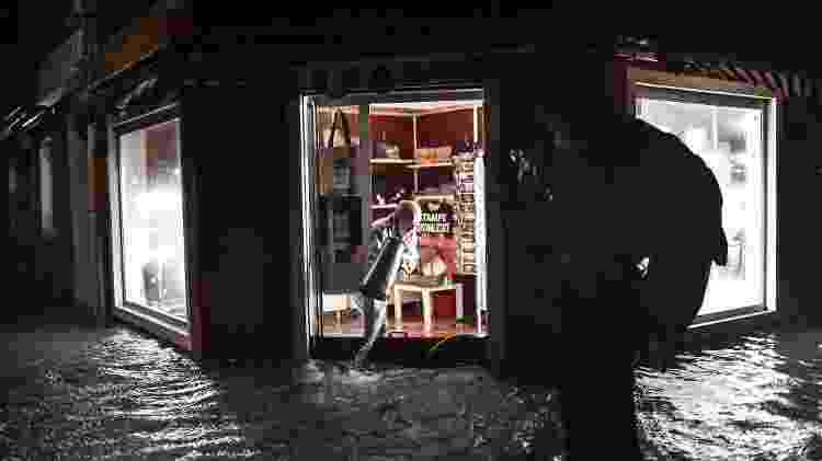 12.nov.2019 - Com baldes, os comerciantes tentavam evitar que a água tomasse seus estabelecimentos durante a inundação - Marco Bertorello/AFP - Marco Bertorello/AFP