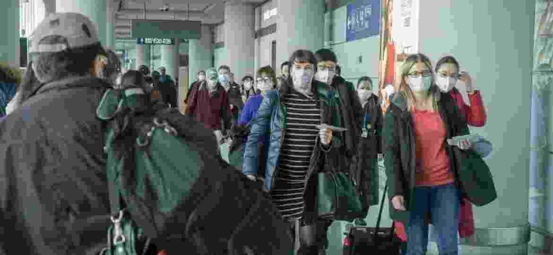 Viajantes com máscara no aeroporto de Beijing, na China - Getty Images