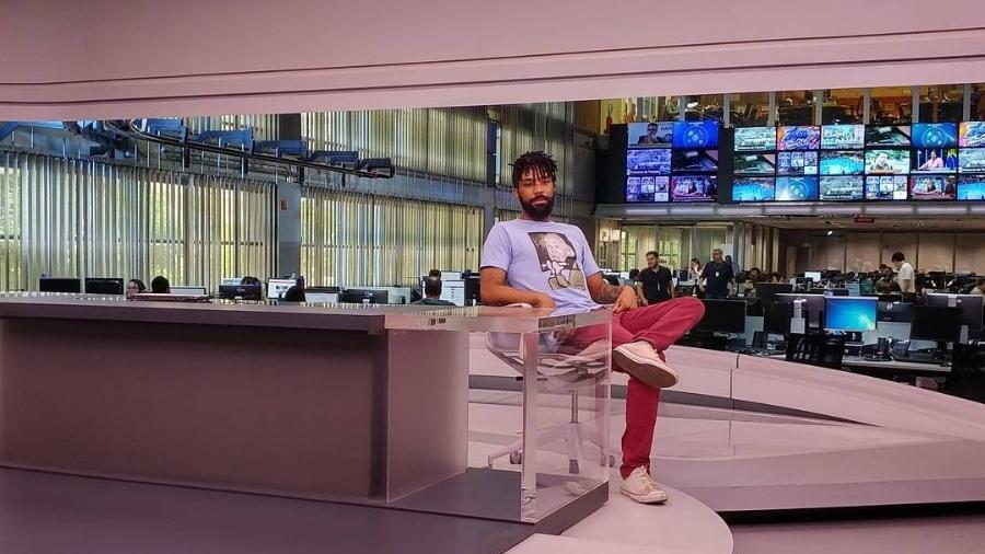 """Diego Rocha posa no cenário do """"Jornal da Globo, sentado na cadeira que foi de William Waack, em SP - Reprodução/Instagram"""