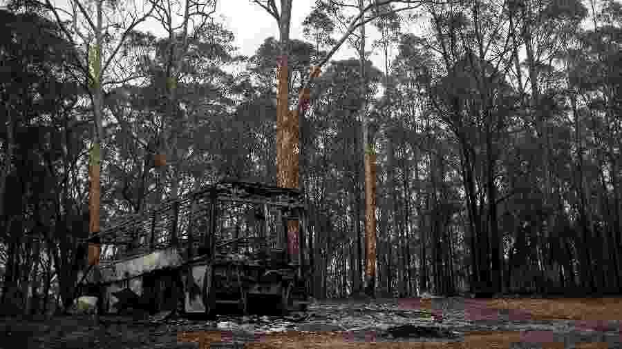 Um ônibus destruído ao lado das queimadas em Mogo, Austrália - Reuters