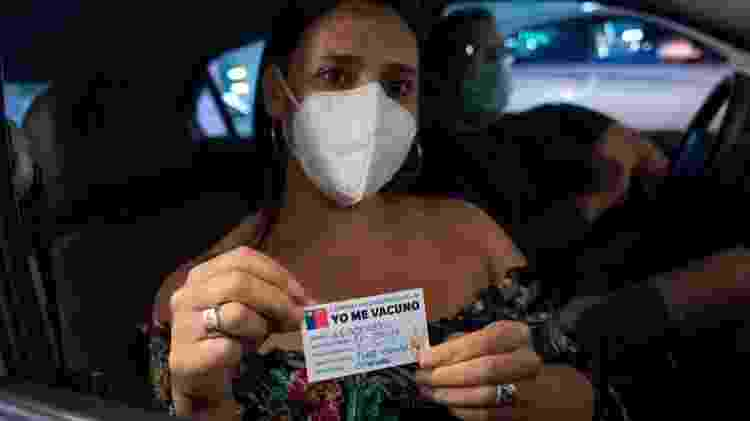 Chilena mostra o cartão de vacinação contra a covid-19. País pretende imunizar 80% da população até julho - Claudio Santana/Getty Imagens - Claudio Santana/Getty Imagens