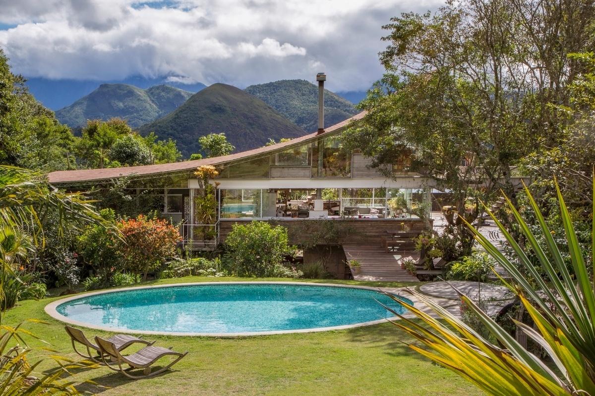 A cobertura curva com 20 m de extensão se destaca em meio às montanhas que formam o cenário para a casa Samambaia, projetada pelo arquiteto Rodrigo Simão. Composto por assoalho de cumaru, manta asfáltica e telhado