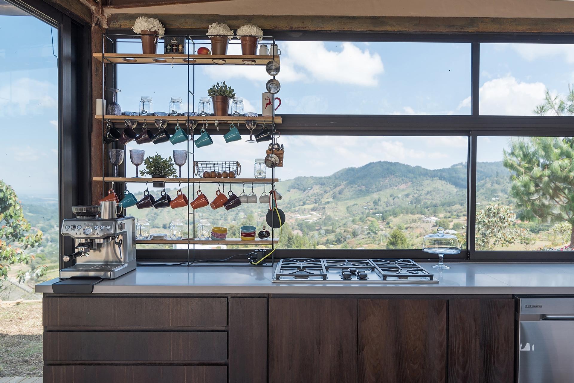 Na cozinha, a marcenaria é revestida com painéis de fibra que imitam a madeira natural e parte dos utensílios pode ficar exposta no louceiro de metal. A arquitetura da casa Gozu, projetada pela equipe do coletivo de arquitetos OPUS, explora a beleza da paisagem através de generosas aberturas