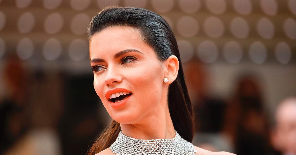 """A modelo brasileira Adriana Lima optou por um elegante sleek hair, também conhecido como """"cabelo lambido"""". Para ter esse efeito, é necessário fazer uso de gel ou pomada para deixá-lo super liso, sem nenhum frizz e com aparência de molhado"""
