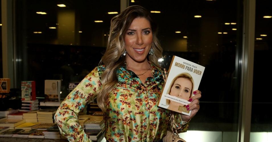 24.ago.2015 - Tati Minerato posa para foto segurando um exemplar da biografia de Andressa Urach,