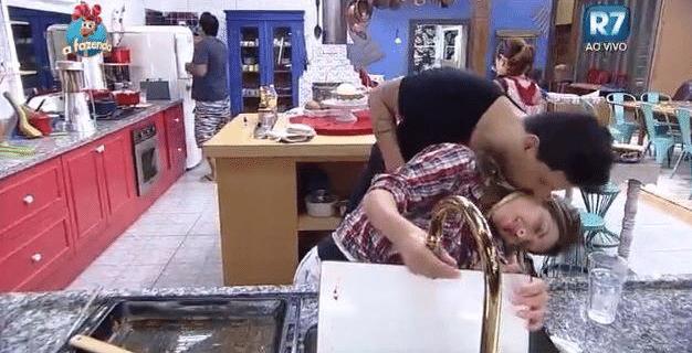 29.set.2015 - A peoa Ana Paula Minerato tenta se esquivar do cantor sertanejo Thiago Servo enquanto lavava a louça