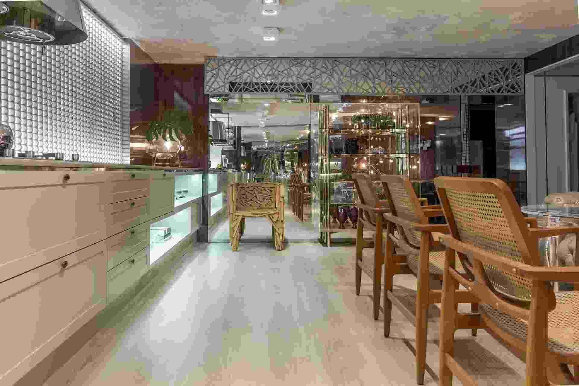 Casa Cor Paraíba 2016 - Para a Cozinha da Chef, Raquel Claudino e Geórgia Suassuna desenharam um painel vazado de aço, que emoldura o topo da parede espelhada. À esquerda, na janela, a cortina Parametre (HunterDouglas) é um painel de ecorresina recortado, que pode ser usado como divisória. Os elementos são contemporâneos e combinam com o mix de acabamentos e estilos de móveis do espaço - undefined