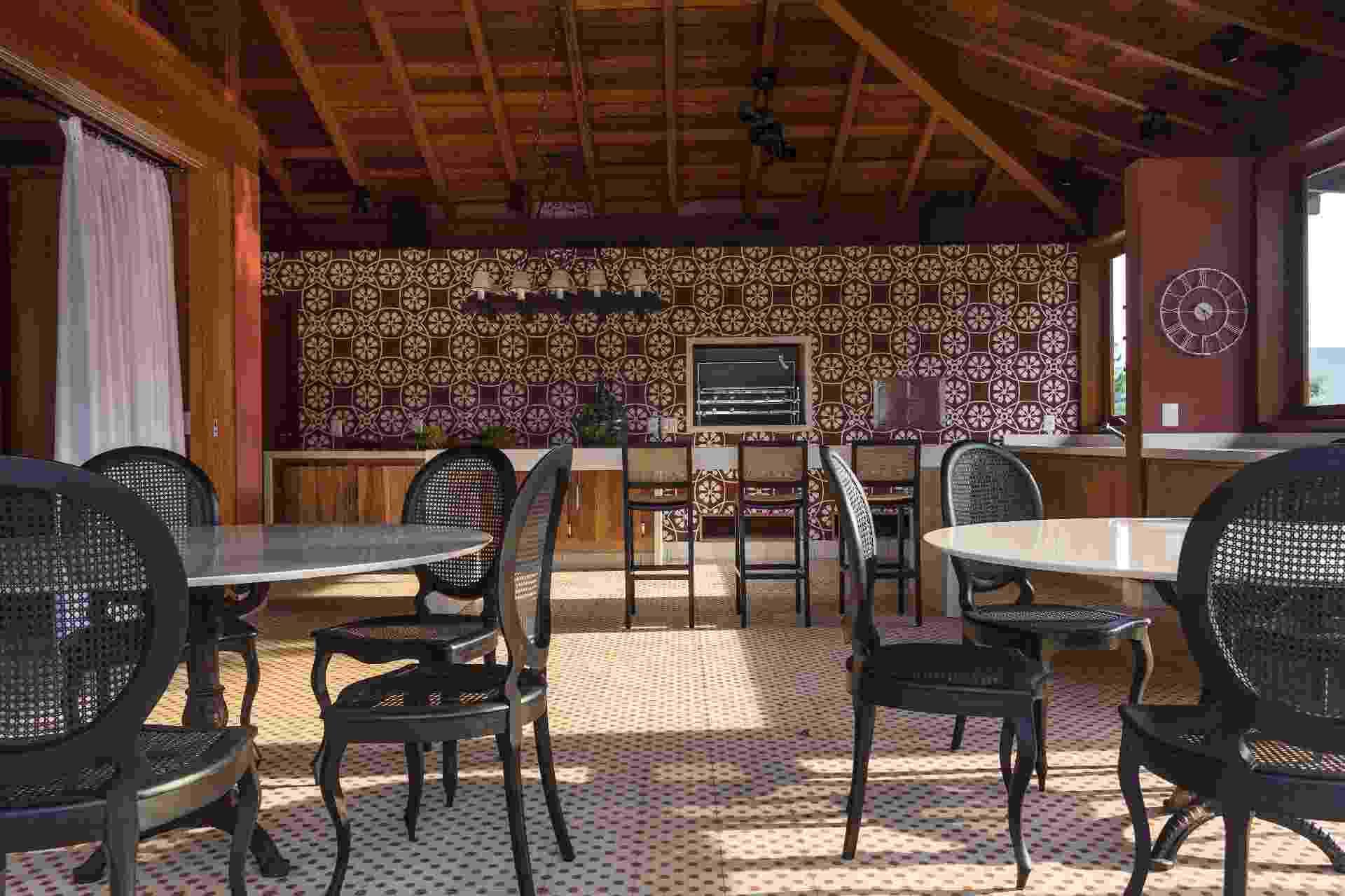 O arquiteto Maurício Karam revestiu a ampla área da churrasqueira com ladrilhos hidráulicos. Os conjuntos de jantar em estilo retrô-rústico e o lustre antigo (sobre a bancada) faziam parte do acervo da família e foram incorporados à decoração - undefined