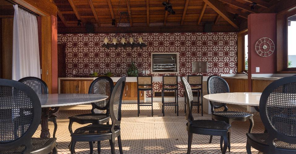 O arquiteto Maurício Karam revestiu a ampla área da churrasqueira com ladrilhos hidráulicos. Os conjuntos de jantar em estilo retrô-rústico e o lustre antigo (sobre a bancada) faziam parte do acervo da família e foram incorporados à decoração