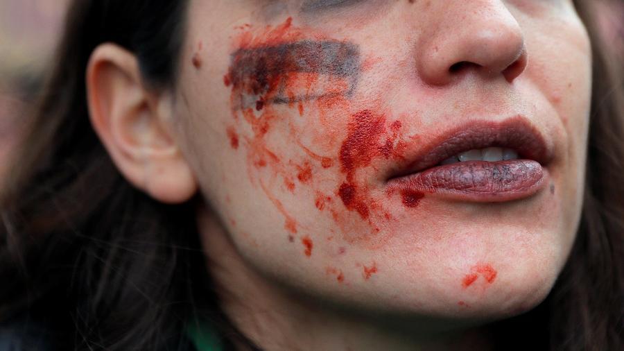 Manifestante faz maquiagem simulando uma agressão física para protestar contra a violência de gênero, em Madri - Susana Vera/Reuters
