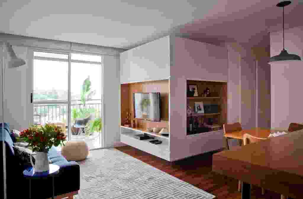 """O apê Cátia tinha, originalmente, uma sala expandida e apenas um dormitório. Para receber mais um morador, foi criado um novo quarto com parede de gesso acartonado, que também fixa a marcenaria em L do living. O móvel, desenhado pelo escritório Iná Arquitetura, """"flutua"""" a 15 cm tanto do piso, quanto do forro - Divulgação"""