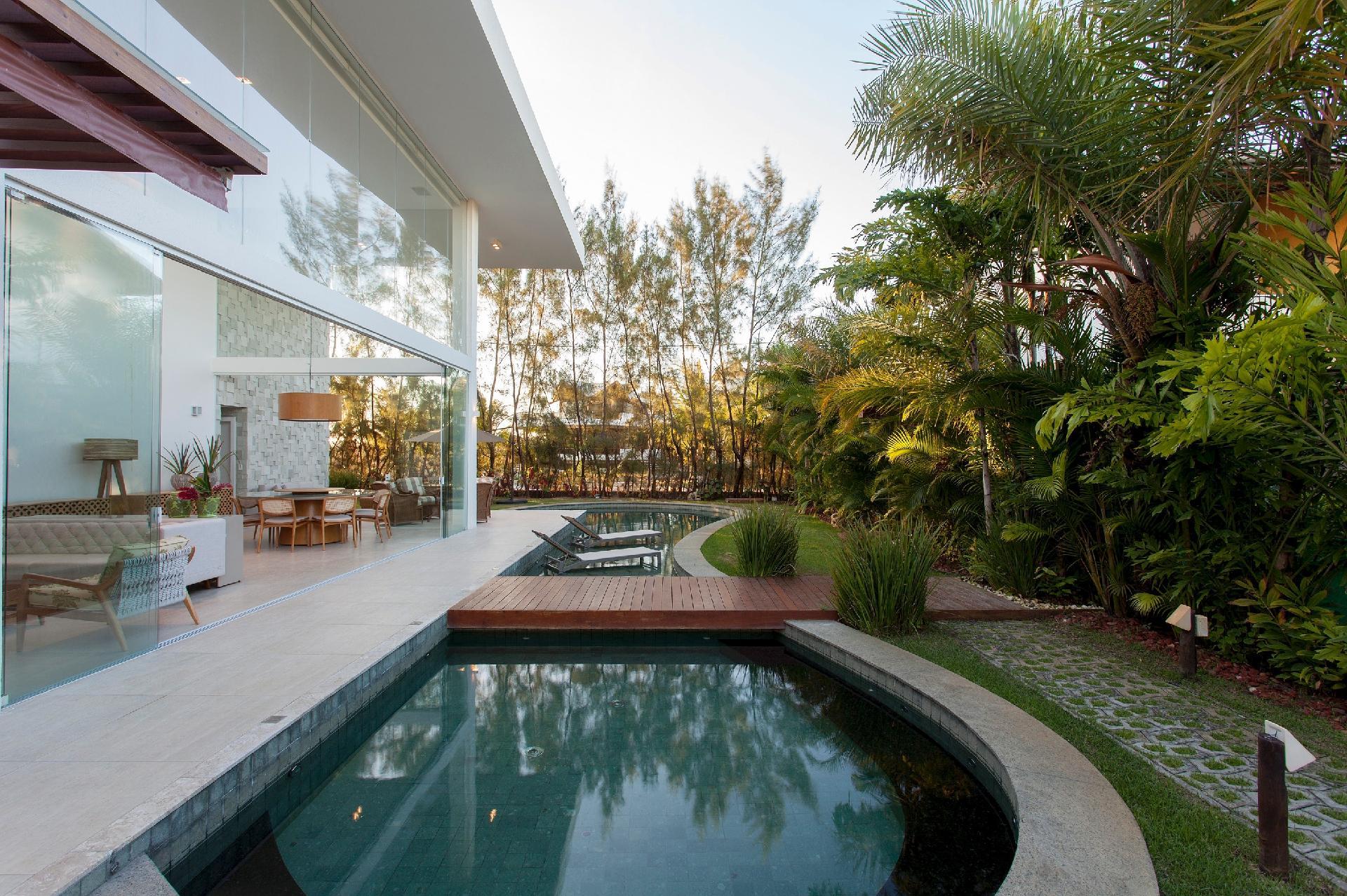 A piscina da casa de praia tem um desenho orgânico e alongado que ?abraça? toda a área social. Nela, a passarela de madeira conecta as salas de estar e jantar ao jardim. A residência em Camaçari (BA) foi desenvolvida pelo arquiteto Sidney Quintela