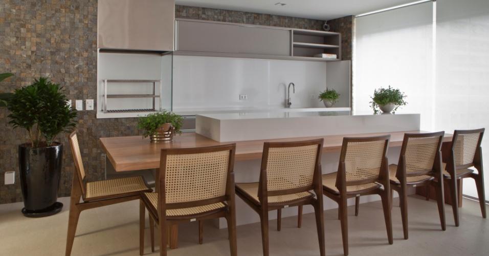 A mesa de jantar em madeira possui uma bancada integrada feita de superfície de quartzo (Silestone) cinza. A combinação de materiais nobres dá um ar elegante à varanda gourmet, assinada por Roberta Banqueri