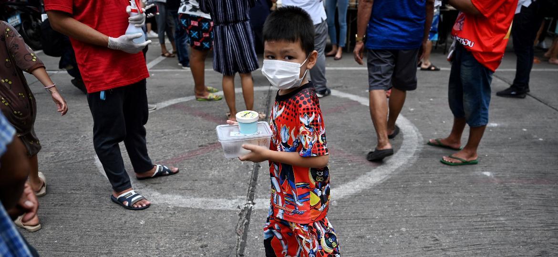 Um jovem residente da comunidade de favela de Klong Toei segura uma caixa de comida feita por chefs com estrela Michelin em Bangkok em 14 de junho de 2021, enquanto as indústrias de alimentos e bebidas, bem como a segurança alimentar entre as comunidades mais pobres da Tailândia continuam em queda livre devido às restrições contínuas do coronavírus  - Lillian SUWANRUMPHA/AFP