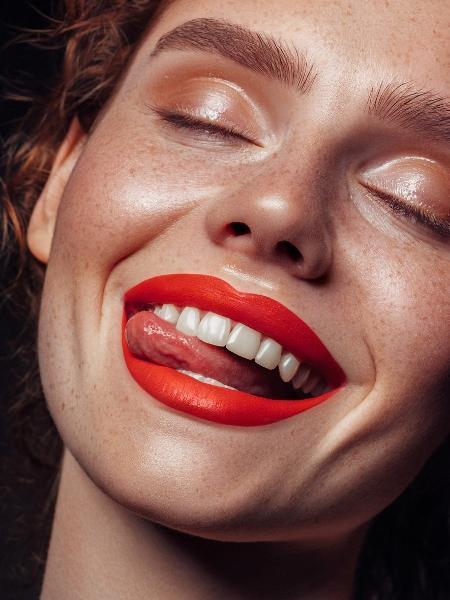 Mulher com batom vermelho - CoffeeAndMilk/iStock