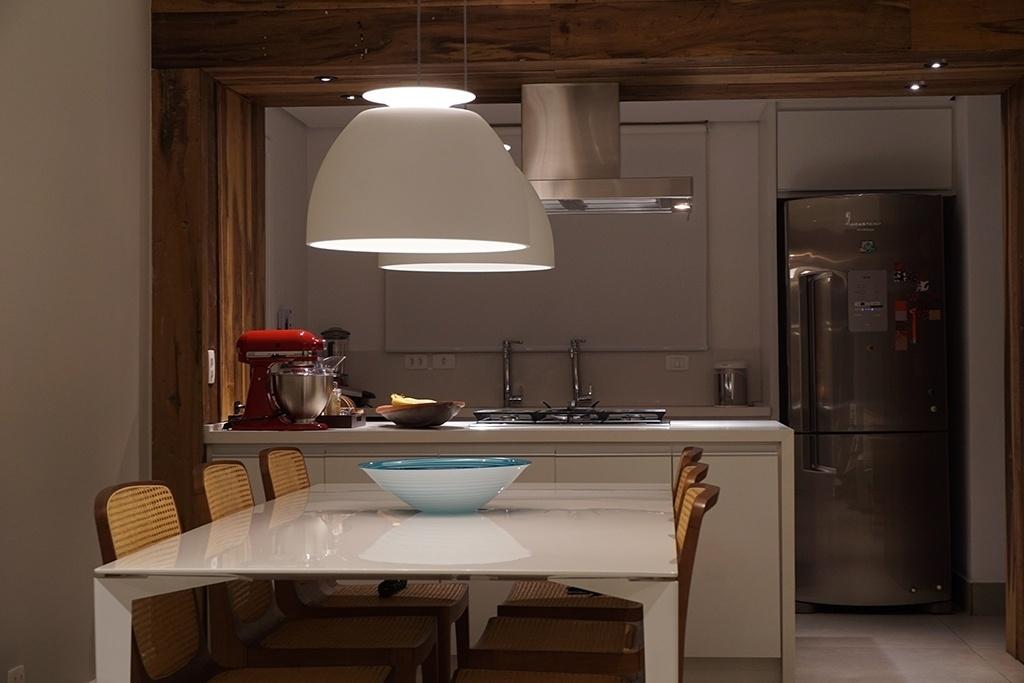 Na cozinha do apartamento de um jovem casal, a arquiteta Daniela Savioli buscou o contraste da madeira de demolição com os acabamentos brancos. Entre as peças, destaque para o par de luminárias sobre a mesa de jantar e as cadeiras com assento e encosto de palhinha