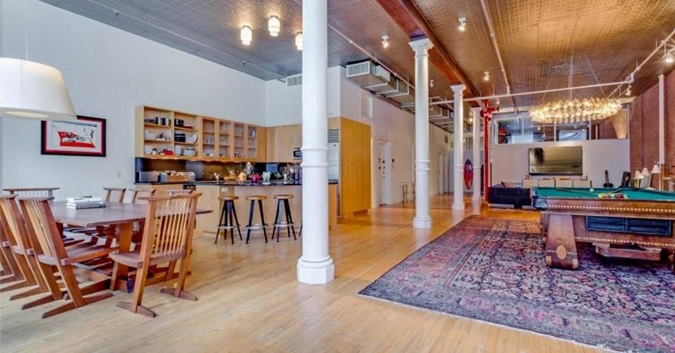 A sala de jantar conta com uma mesa de madeira com oito cadeiras. A cozinha integrada é equipada com armários planejados, que deixam louças, objetos e utensílios à vista. O loft do cantor Adam Levine e da modelo Behati Prinsloo está à venda por cerca de R$ 20 milhões, em Nova York, Estados Unidos